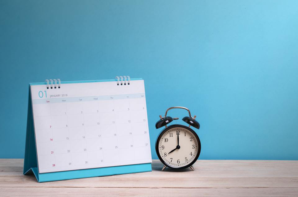 Close-Up Of Calendar With Alarm Clock On Wooden Table Against Blue Background