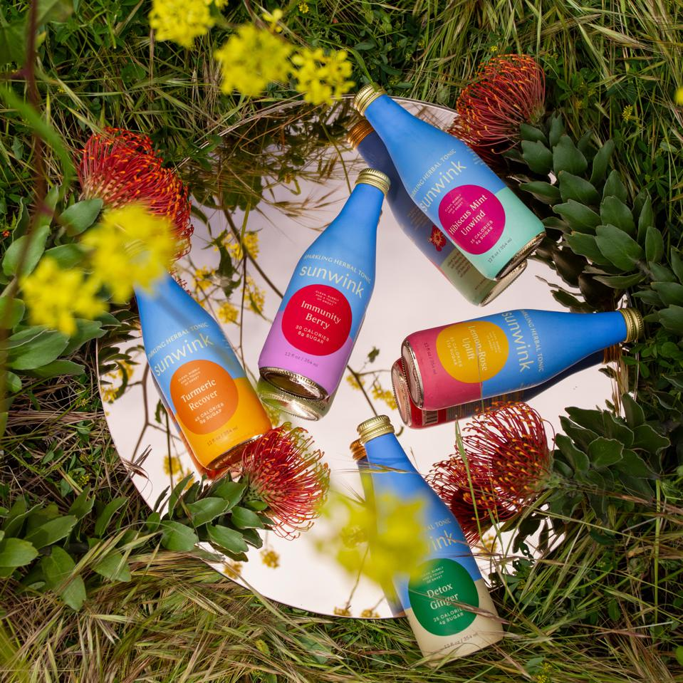 A selection of colorful Sunwink bottles on a glass mirror in the garden.