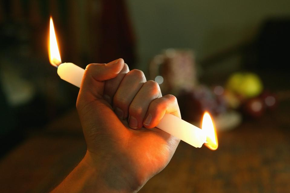 An person burning a candle at both ends, which means to do more than one ought to do