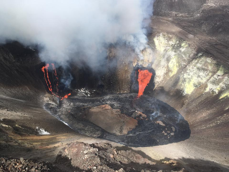 Lava pours from the side of the pit crater walls.
