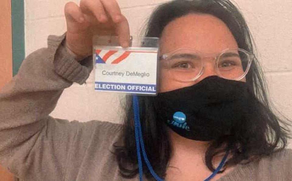 UNICEF USA National Council member Courtney holds up her election official name tag before volunteering as a poll worker in Newtown, Connecticut on November 3, 2020.