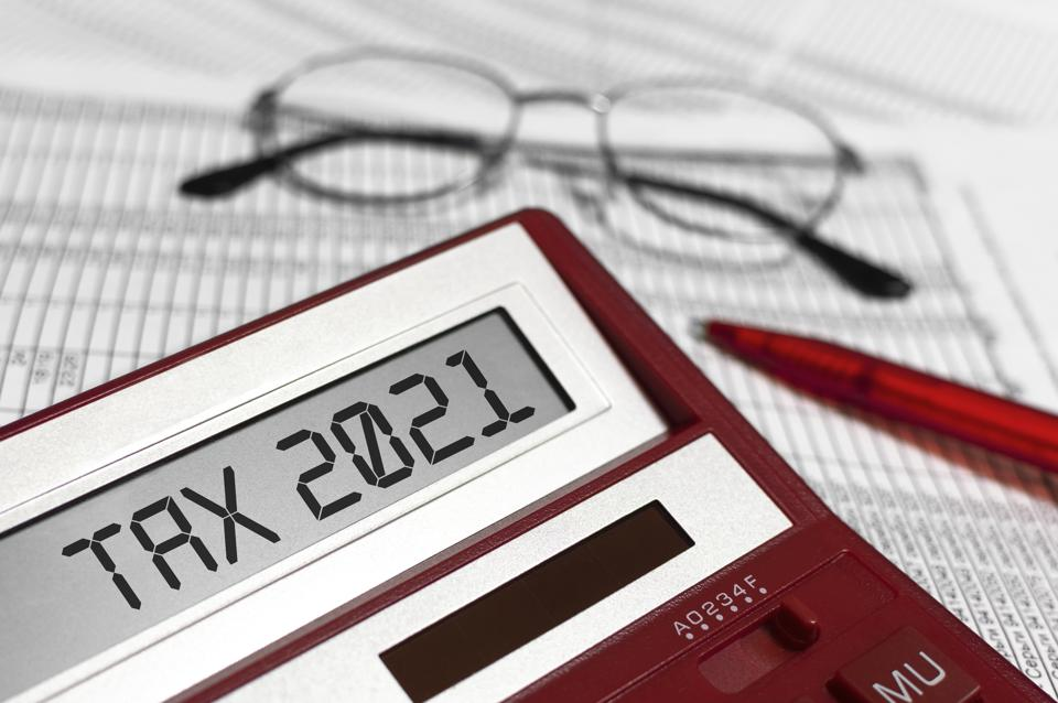 Word Tax 2021 on calculator. Glasses, pen and the calculator on documents. The concept of financial stability,Income Statement