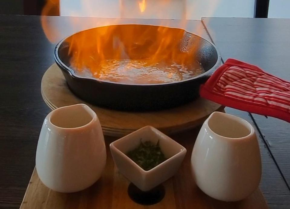 Close up of Flaming Fried Cheese being fired up in a cast iron skillet