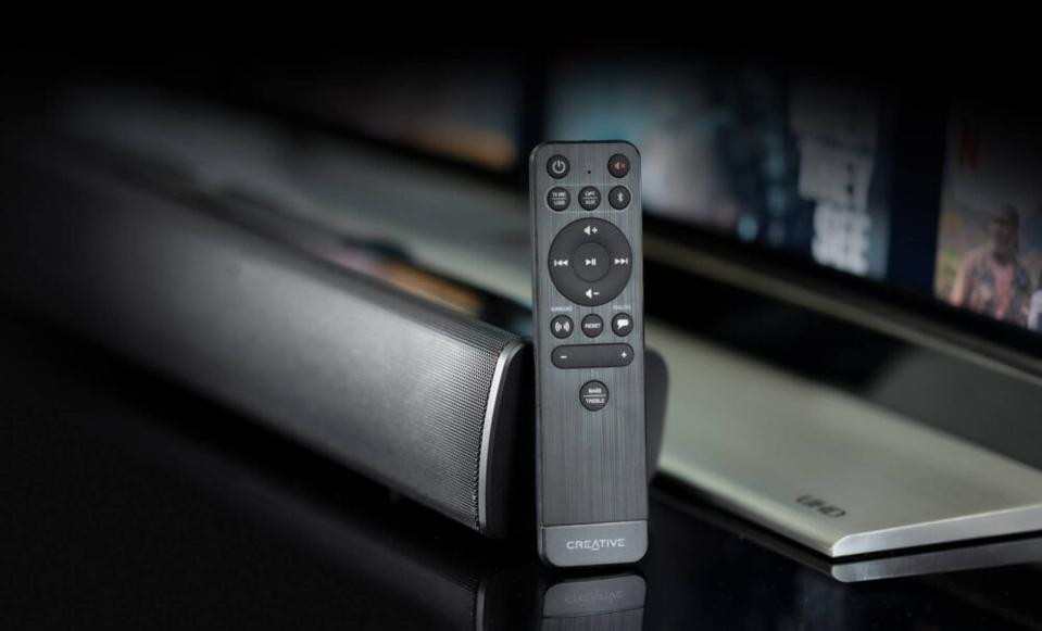 Remote control propped up on the end of the Creative Stage V2 sound bar