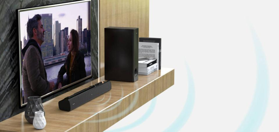 Creative Stage V2 on a shelf in front of a TV with subwoofer unit