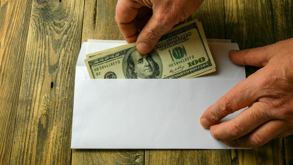 Human hands put two one hundred dollar bills in cash into white paper envelope that lies on brown wooden table. Concept of saving money or corruption and shadow economy.