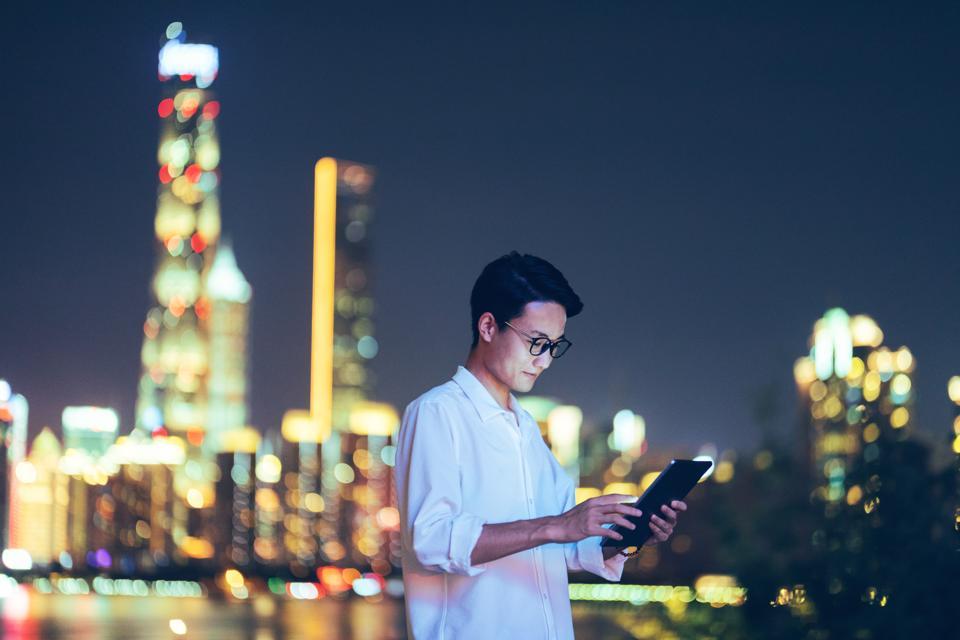 Young Asian businessman using digital tablet, Shanghai, China