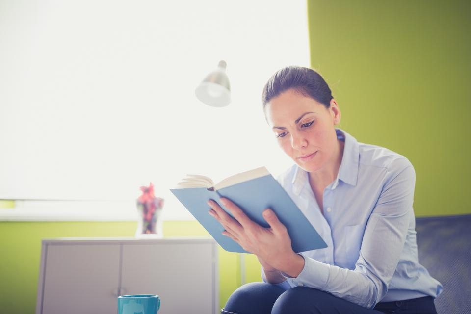 Businesswoman reading book in office library