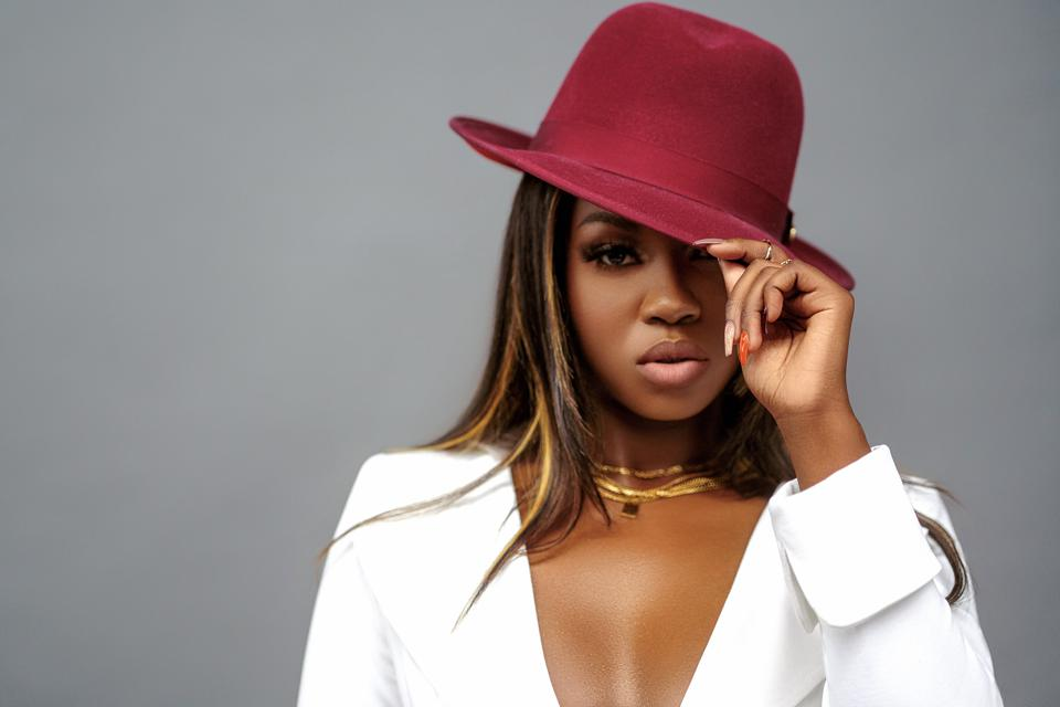 Faith Stowers poses while wearing a hat.