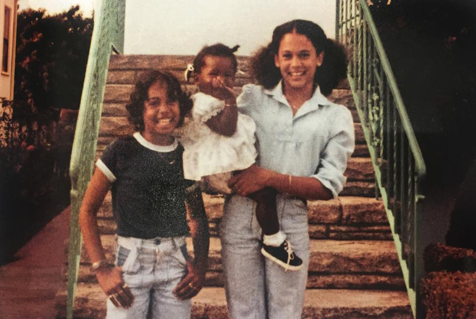 In front of Regina Shelton's house, a young Kamala Harris carries Saniyyah Smith, the granddaughter of Regina Shelton with her sister Maya in the summer of 1978 in Berkeley, Calif.