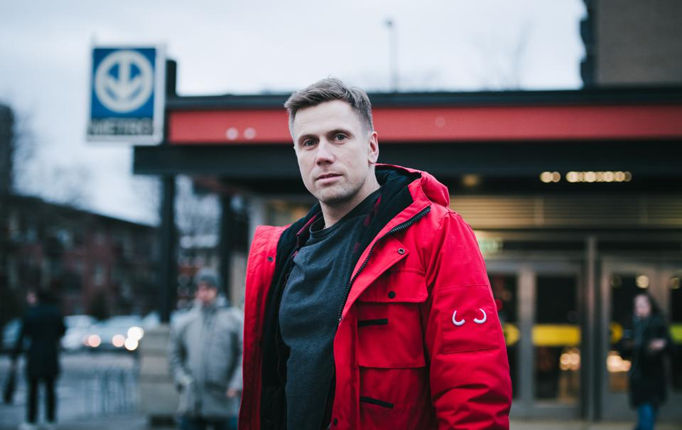 James Yurichuk, CEO of Wuxly Movement, stands outside a subway station in a red parka.