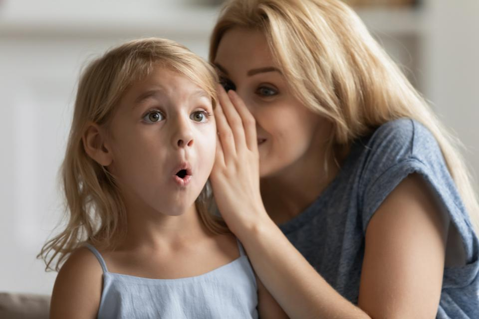 Young mother tell secret to surprised little daughter