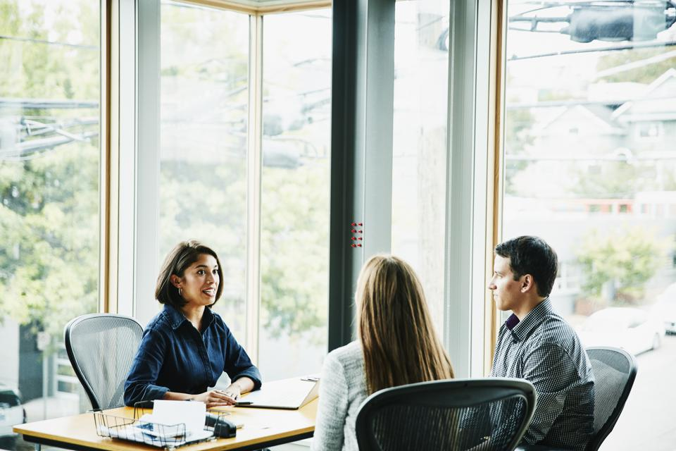 Smiling businesswoman in discussion with clients at office workstation
