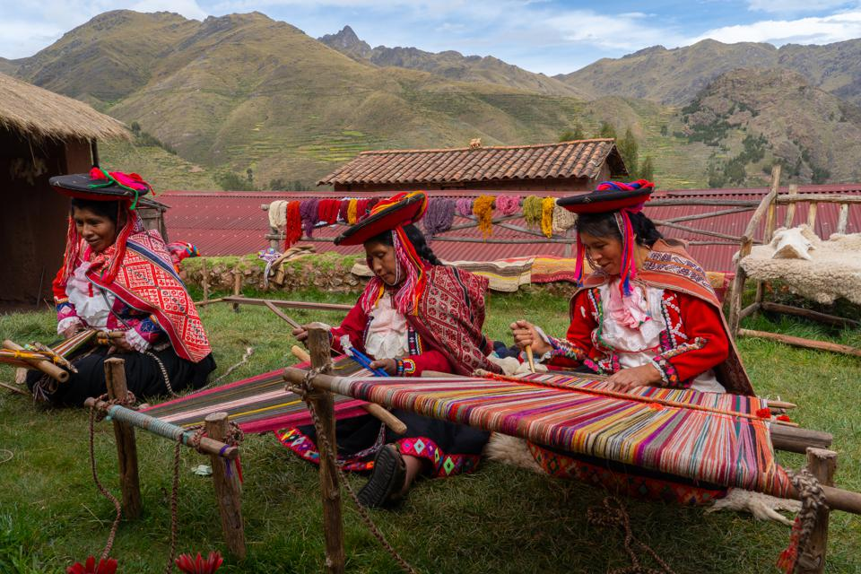 Three local Peruvian female weavers csitting on the ground, reating colourful alpaca wool in the Sacred Valley.l Releases and Property Release)