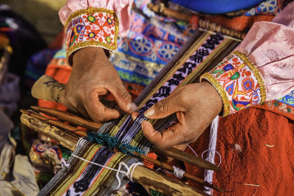 Close up of a Peruvian woman weaving textiles near Colca Canyon, Peru