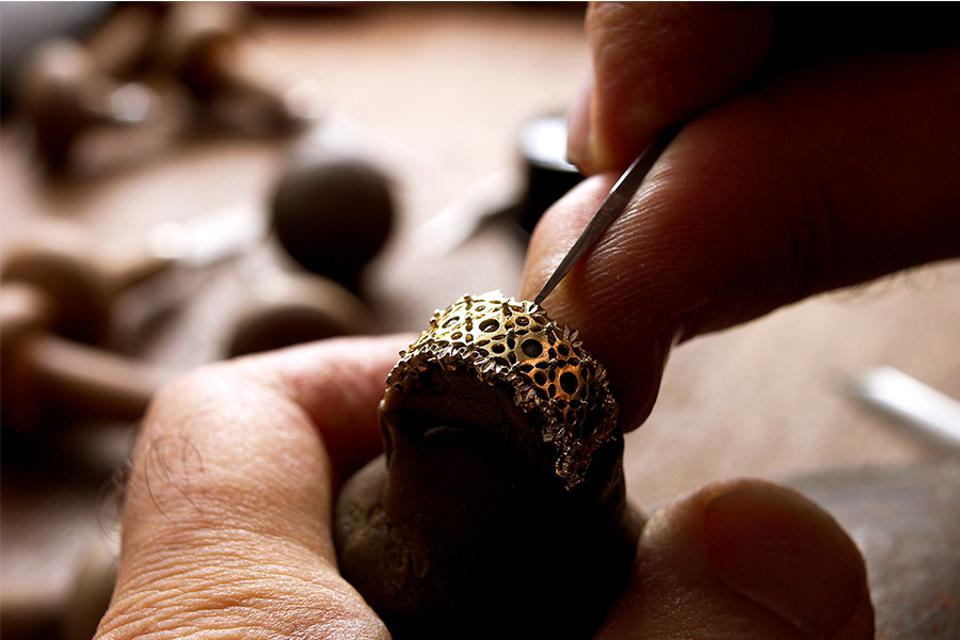 An artisan engraves a ring, a time-consuming and delicate technique