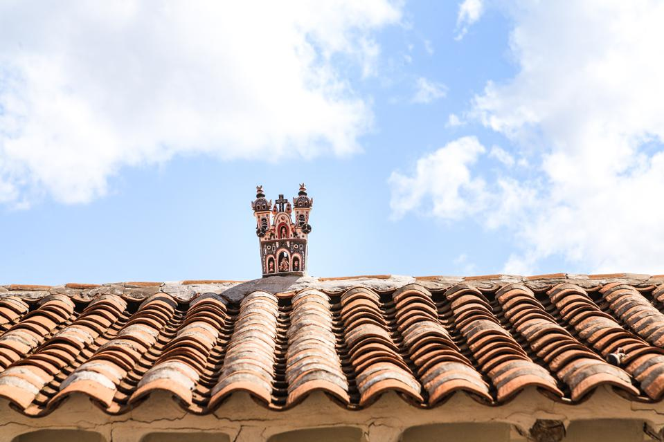 A small hand-carved church on an Andean rooftop