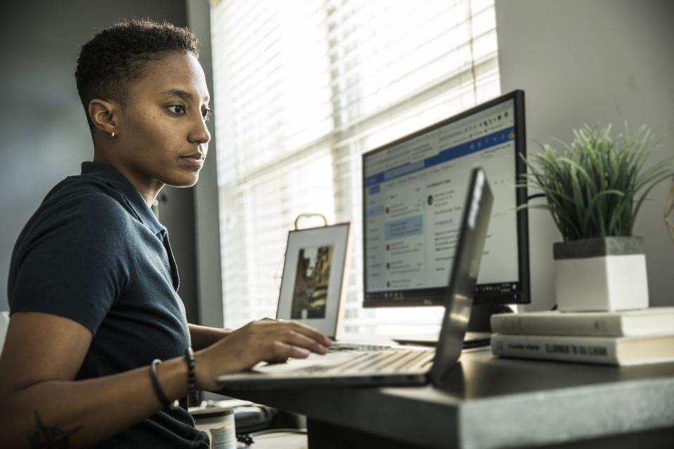 Young woman working on desktop computer at home