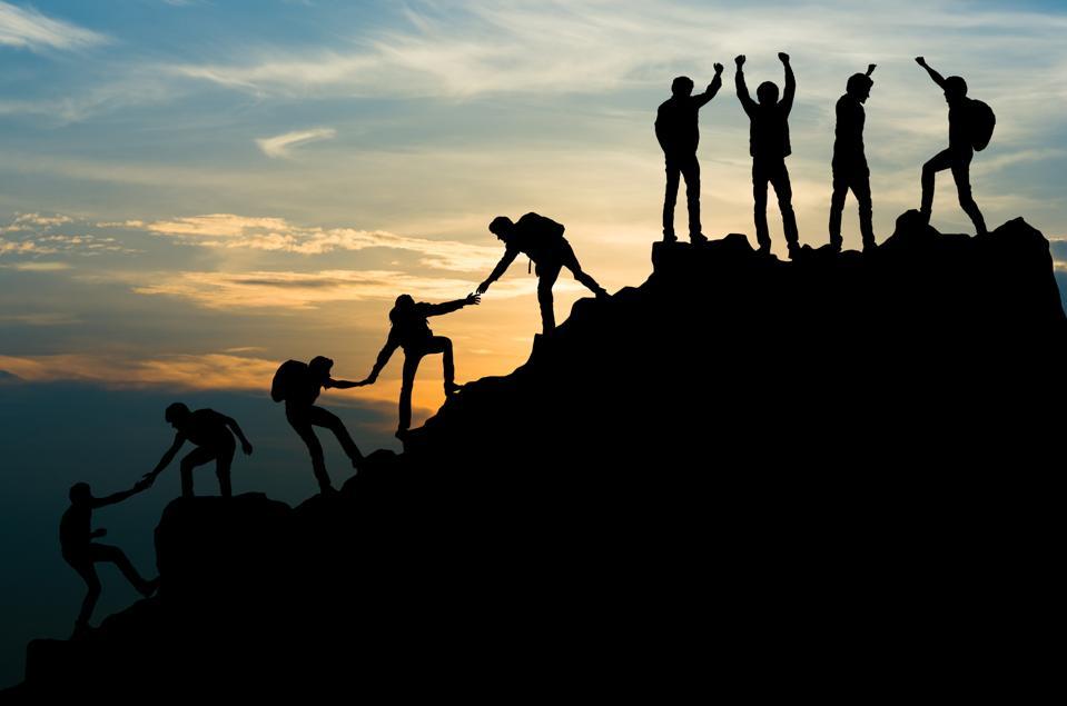 Group of people on peak mountain climbing helping, team work