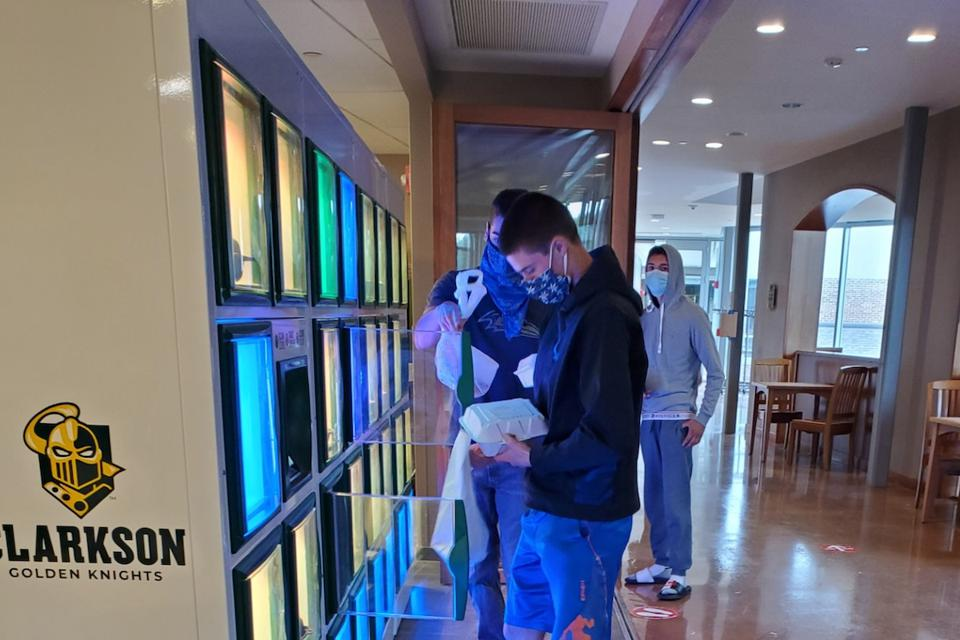 Picture of students opening food lockers at Clarkson University.