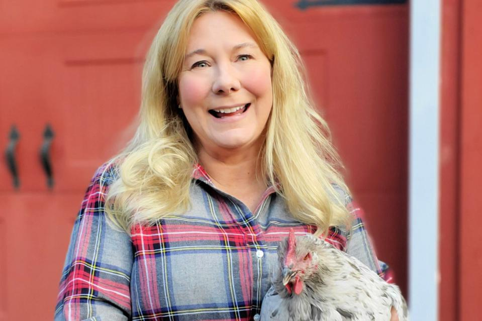 White woman with long blonde hair wearing plaid shirt holding a chicken.