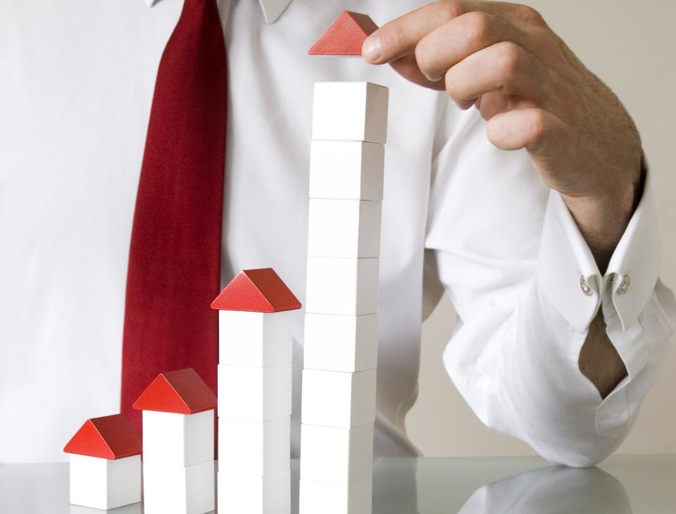 Businessman with building blocks to denote growth