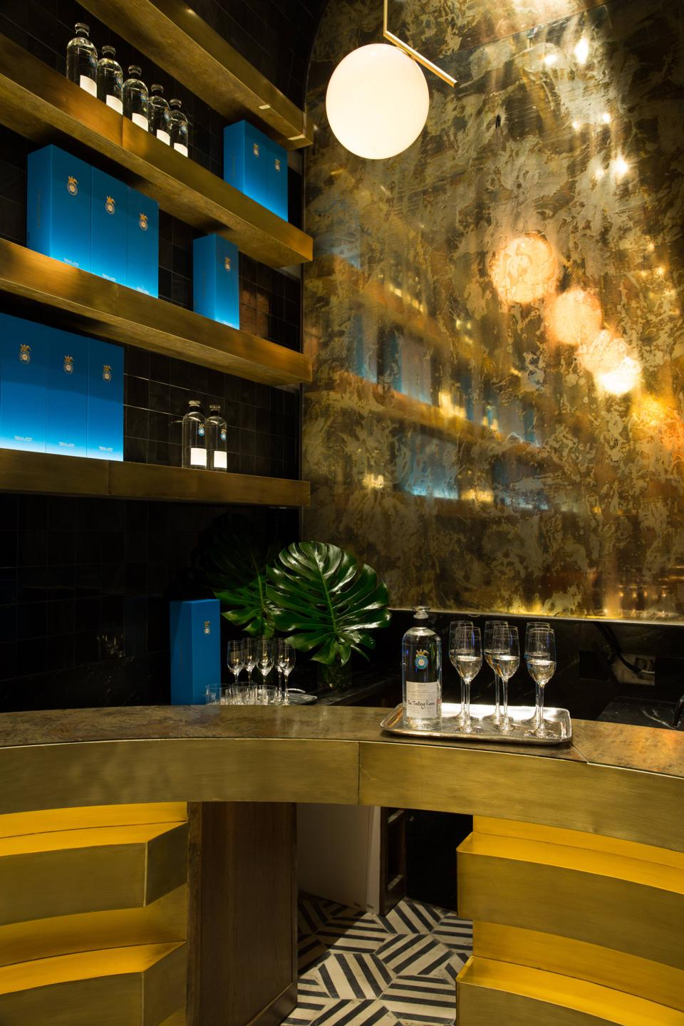 The tasting room, with a gold bar, mirrored wall and an opposing obsidian-tiled wall.