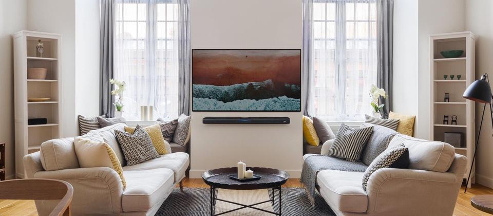 Living room with flat-panel tv and wall mounted Polk React sound bar