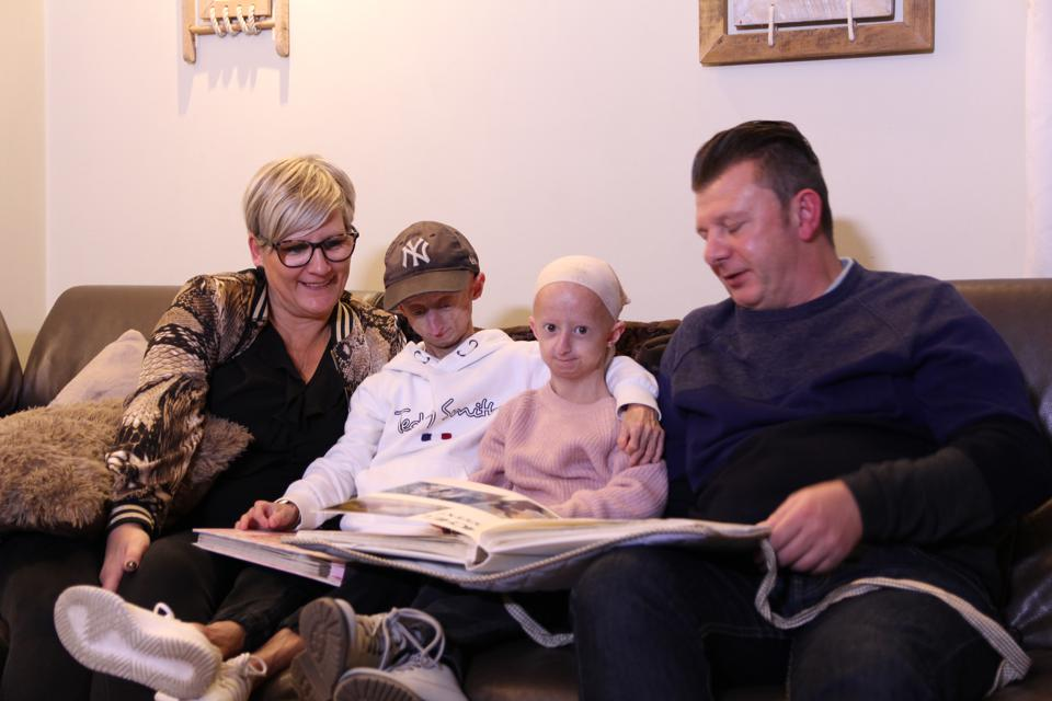 Siblings, Michiel and Amber Vandeweert, who were born with Progeria, sit with their parents Godelieve (left) and Wim (right), looking at family photographs  PHOTOGRAPH BY Mert Beken / Barcroft Images.