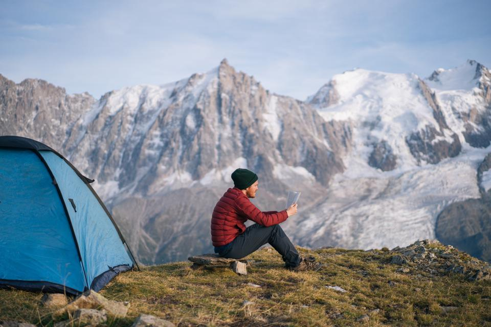 Hiker relaxes in mountain landscape, reads book