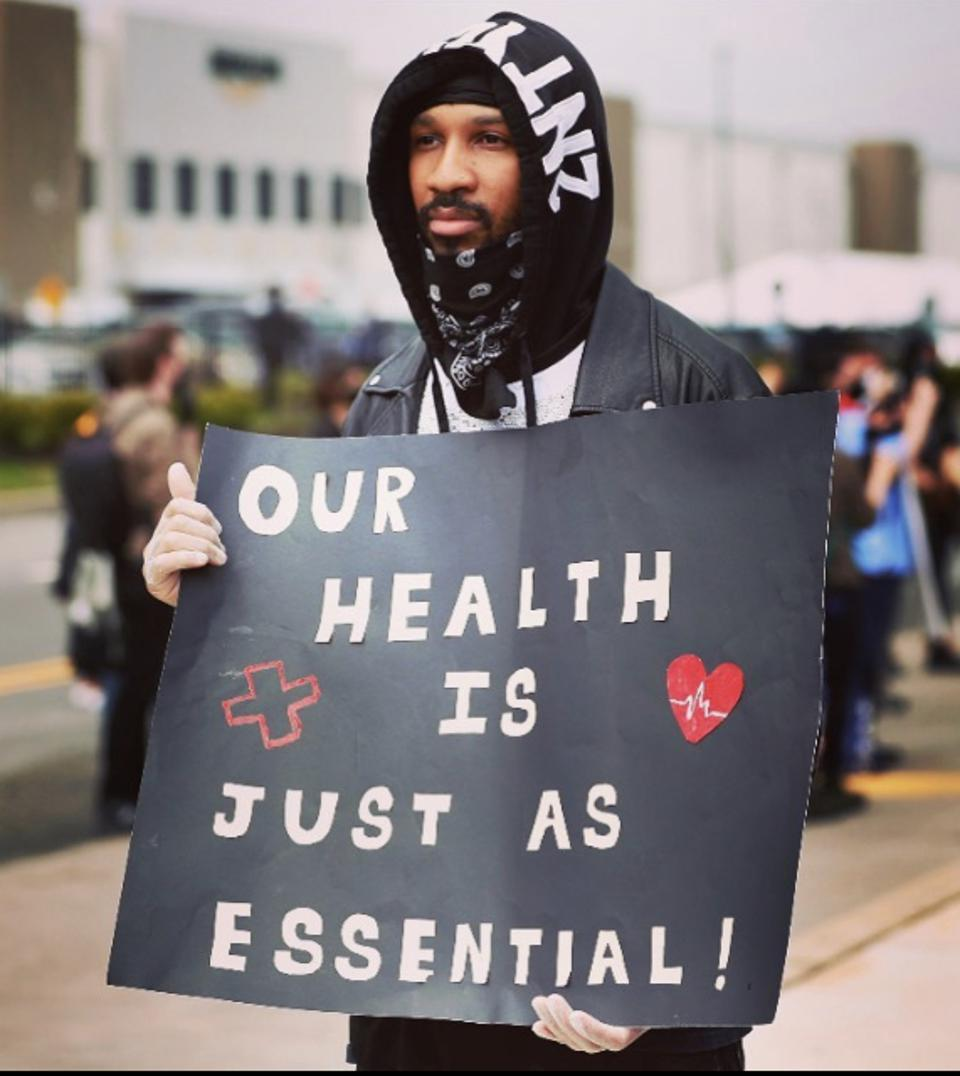 A young Black man holds a banner that states ″Our health is just as essential.″