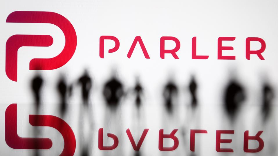 Parler logo in front of silhouette of people