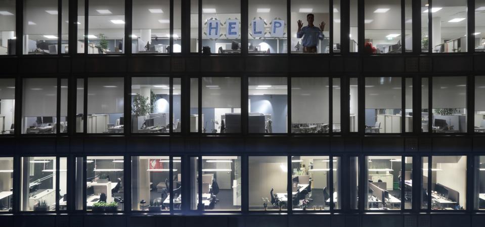 Office block windows at night, man asking for help