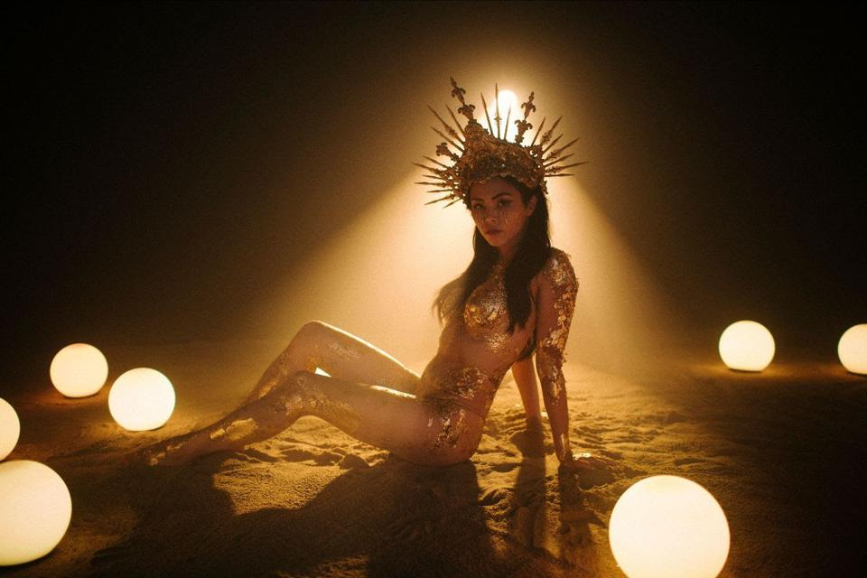 A backlit woman covered in gold leaf, wearing a headdress.