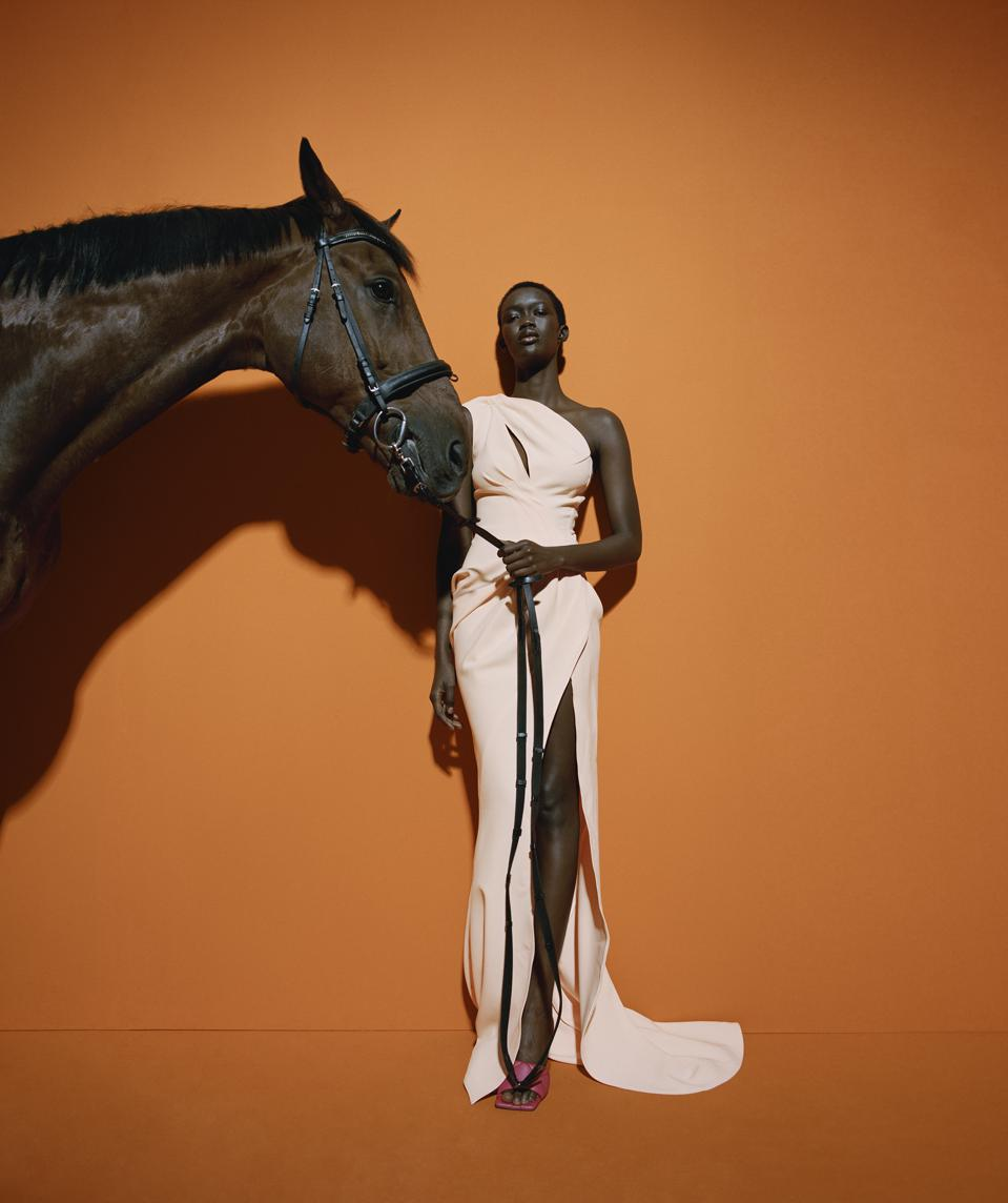 A model wearing a long one-shoulder pale peach gown holds a horse's lead in her hand in a Mytheresa ad.