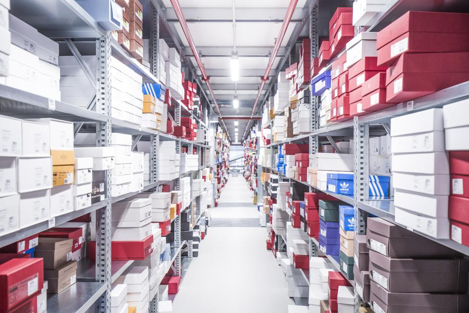 Red, blue and white boxes neatly stacked on metal shelves in Mytheresa's logistics center.