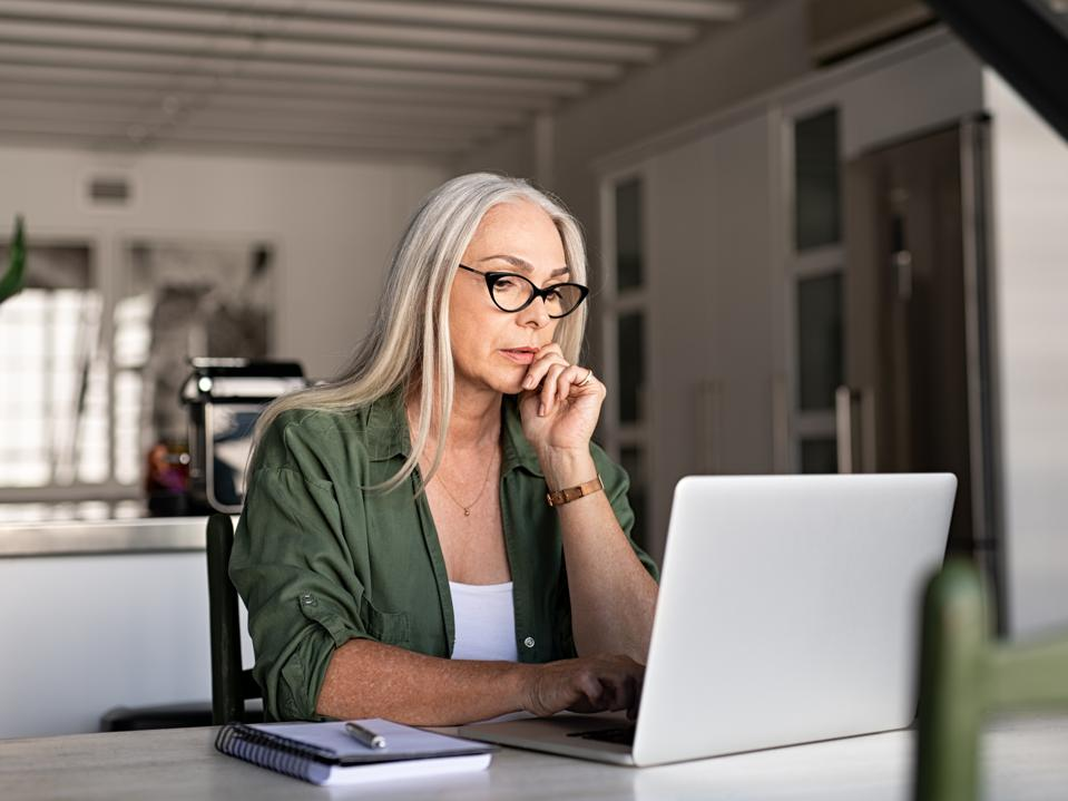 Lovely gray-haired woman works on computer, happily not marginalized for her sex or age