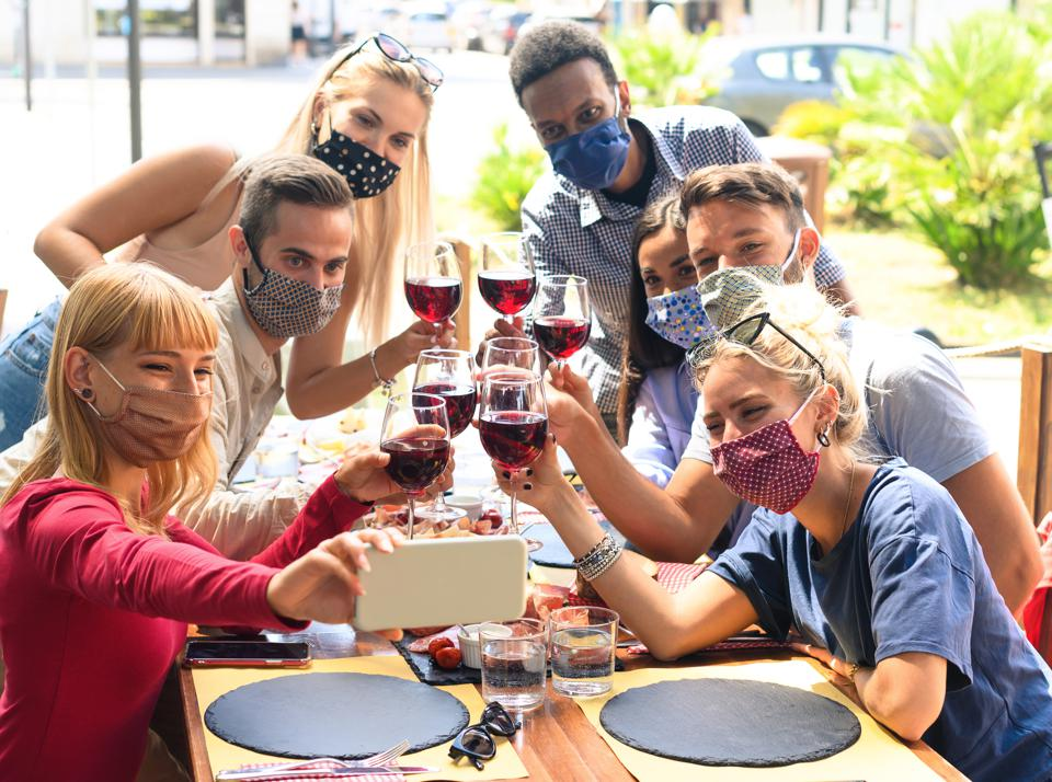 Friends with face mask taking selfie while toasting red wine at restaurant - Young people having fun with drinks -  The new normal lifestyle concept