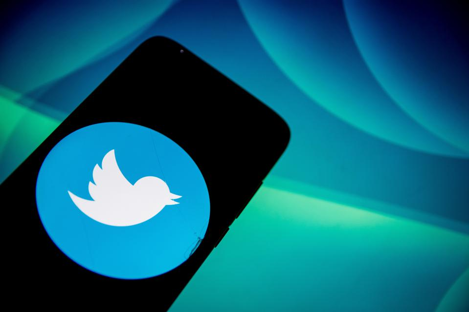 In this photo illustration Twitter logo is displayed on a...