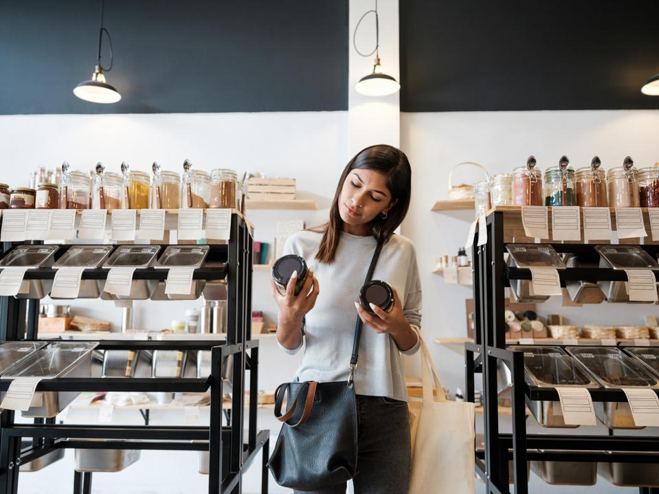 Young woman holding jars in zero waste store