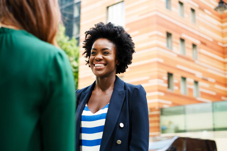 Two women having business discussion, smiling