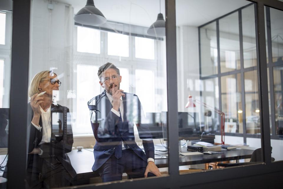 Businessman and businesswoman looking at drawing on glass pane in office