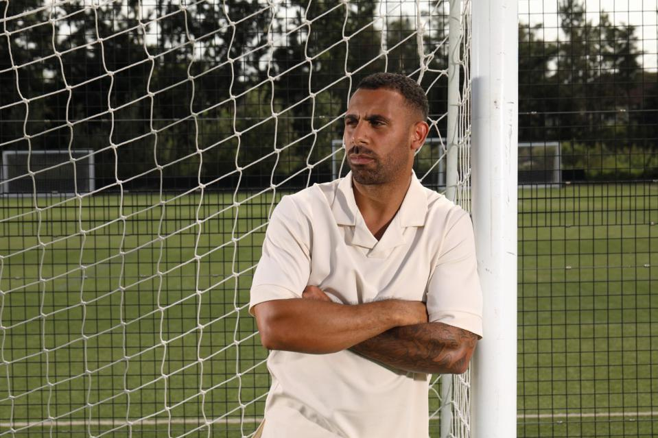 Anton Ferdinand stands in a soccer goal in front of a fence and a training pitch. A press shot for the documentary Anton Ferdinand: Football, Racism and Me