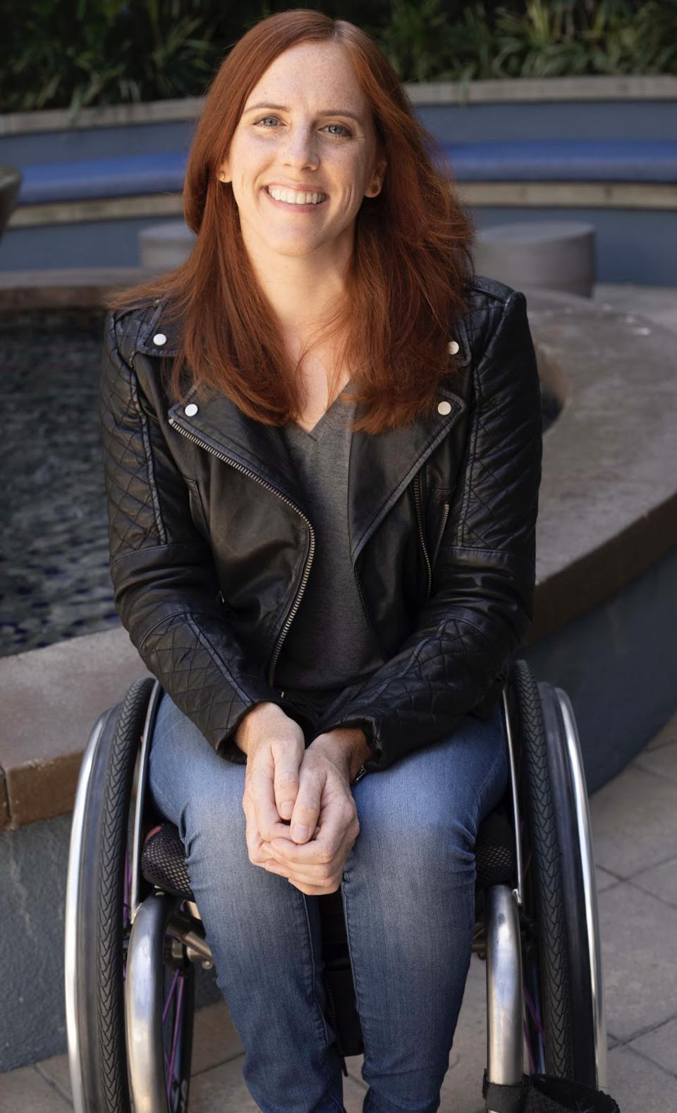 A white woman with red hair smiles while sitting in a wheelchair.