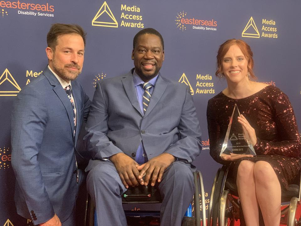 A white woman in a wheelchair sits next to a black man in a wheelchair and a white man.