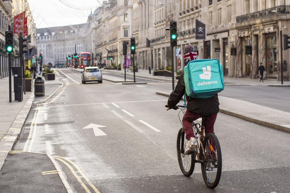 Deliveroo courier rides along Regent Street delivering
