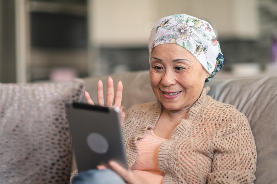 Woman with cancer video chats with friends on digital tablet