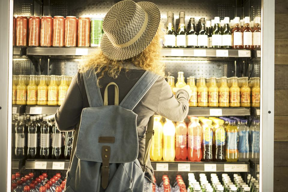 Travel woman viewed from back choosinf beverage in a fresh fridge - airport or station bar concept and traveler passenger choosing drinks - modern lifestyle backpack people buying drinks bottles
