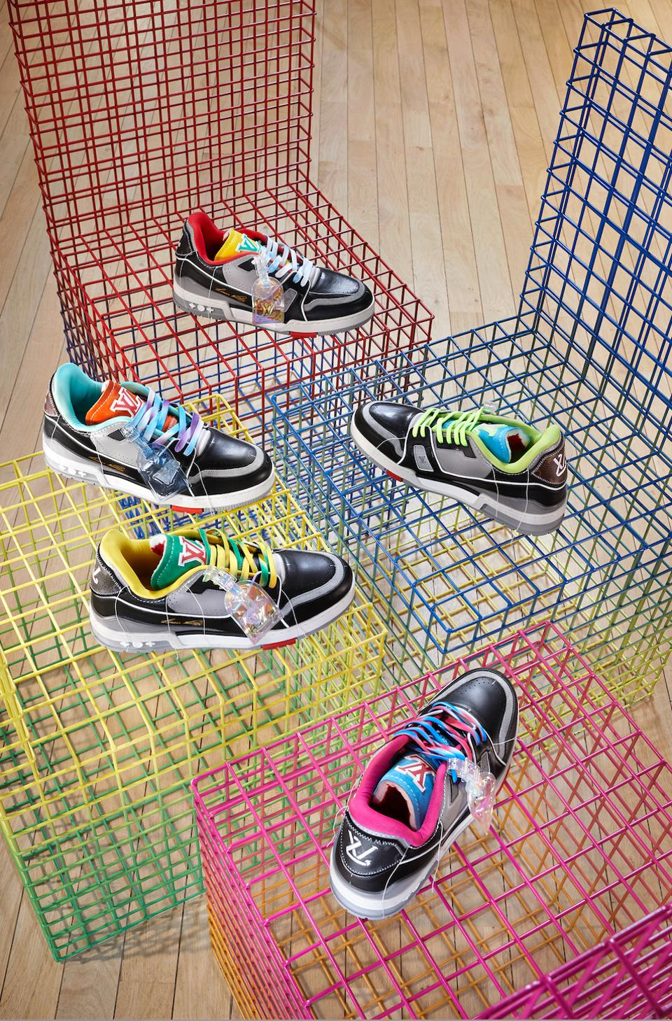 Five pairs of mule-colored Louis Vuitton men's trainers on colored wire crates