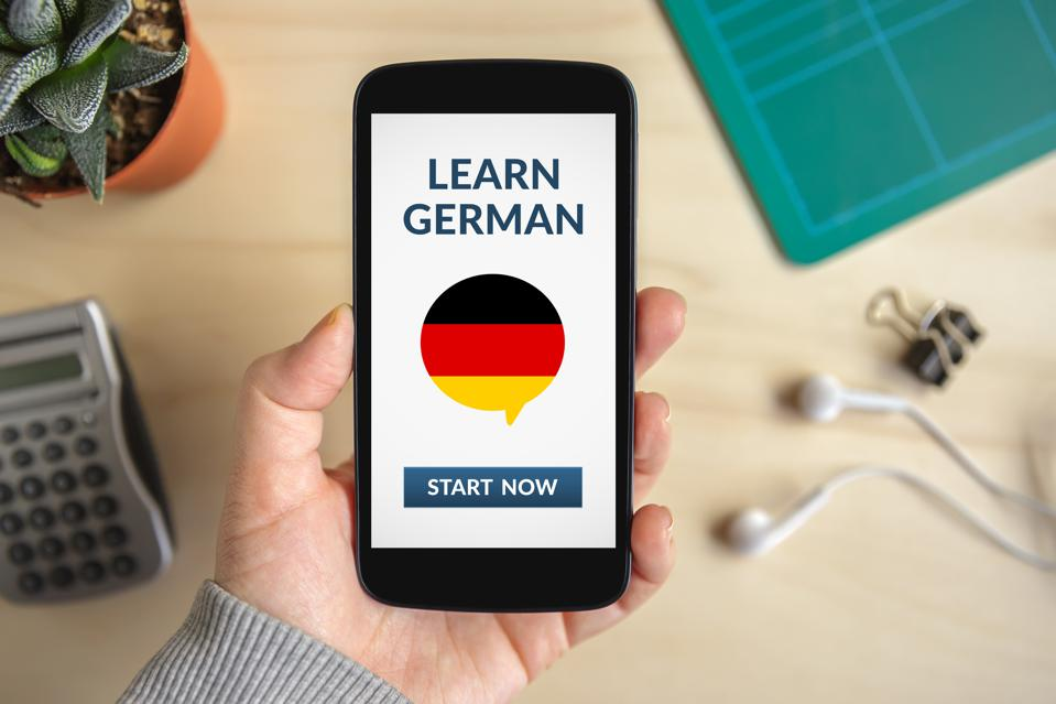 Hand holding smart phone with learn german concept on screen